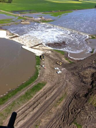 Aerial view of the Portage Diversion looking north with heavy equipment shoring up east side dike.