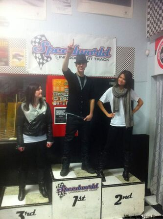 Justin Bieber (centre), Selena Gomez (right) and an unidentified woman take the podium Friday after Bieber and Gomez took a few spins around the tracks at Speedworld Indoor Kart Track.