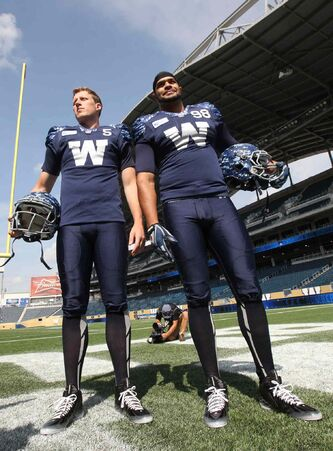 Winnipeg Blue Bombers QB Drew Willy, left, and DE Jason Vega show off the new Signature Jersey at Investors Group Field this afternoon. The Signature Jersey rounds out the Bombers' uniform collection as an alternate jersey that will be worn once, at home on Friday, August 22nd against the Alouettes..