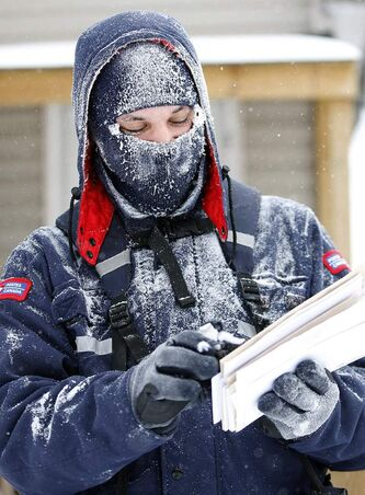 A snow covered Canada Post worker delivers the mail. Extreme cold weather has delayed vehicles from getting mail to carriers for delivery.