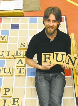 Big Games founder Sean Strachan poses with his giant version of Scrabble. The tiles are bigger, but, alas, the points are the same.
