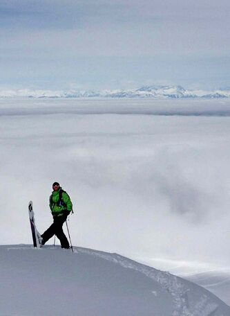 "Kashmiri mountain guide Javed Reshi stands on top of a boulder below the ""Avalanche Wall"" while guiding at Gulmarg."