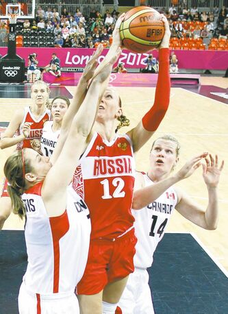Russia's Irina Osipova (12) fights for the ball with Canada's Courtnay Pilypaitis (left) and Chelsea Aubry (14). Russia eked out a 58-53 win.