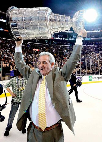 Los Angeles Kings coach Darryl Sutter hoists the Stanley Cup after beating the New Jersey Devils 6-1 during Game 6 of the NHL hockey Stanley Cup finals, Monday, June 11, 2012, in Los Angeles. Sutter says every team in the playoffs has a chance to win the Stanley Cup because of the salary cap.The Sutter-led Kings proved that last year, becoming the first team seeded eighth to win an NHL title.   THE CANADIAN PRESS/AP/Mark J. Terrill