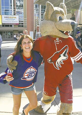 FAR LEFT: A Winnipeg Jets fan has fun with Howler, the Phoenix Coyotes mascot, outside the Jobing.com Arena.
