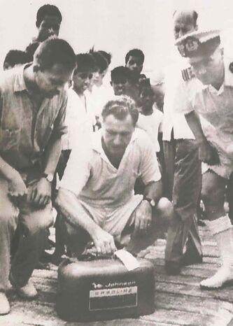 Nelson Rockefeller (centre) examines a gas can picked up by the Dutch navy that may have been Michael's.