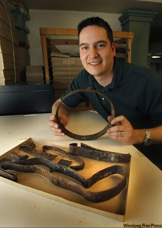 Archeologist Perry Blomquist shows keg hoops, some bent as tools, found at site.