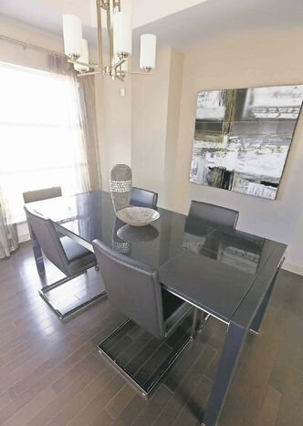 A front-oriented formal dining room has been outfitted with a huge picture window and tray ceiling chandelier.