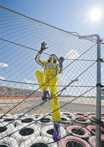 Helio Castroneves celebrates his win by climbing the turn one fence at the Edmonton Indy race on Sunday.