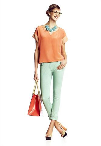 A model wears a designer silk top, coloured denim, a floral statement necklace and peep-toe platform sandals and carries a structured tote from Winners. Bright colours are among the hot hot style trends for spring, but paler pastel hues continue to have a presence. (Winners-Chris Nicholls)