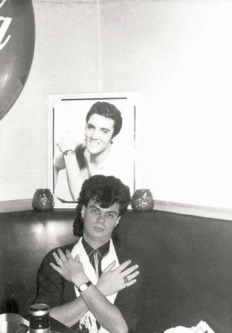 Robert Zaporan poses underneath a photo of Elvis.