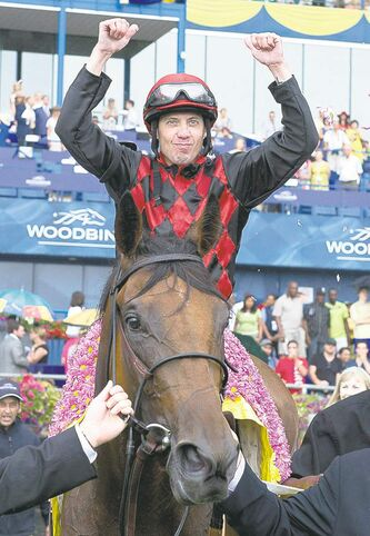 Jesse Campbell celebrates his win of the Queen's Plate atop Midnight Aria.