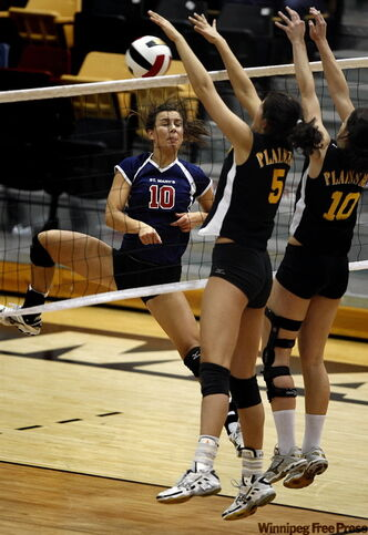 Crocus Plains defenders Angelica Quiring (5) and Mary Thomson reject St. Mary's Academy's Erica Sandor's spike.