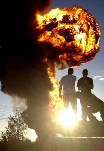 Onlookers watch a fireball rise from Speedway International, a company that was storing biofuel, in 2012.