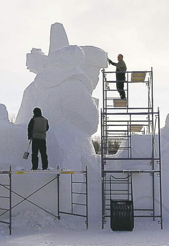Dave Maddocks (right) and Barry  Bonhan put the finishing touches  on the snow sculpture entrance  titled Fiddle Me Home.