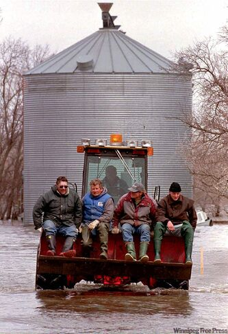 Manitoba farmers (from left) Bernie Ross, Jake Warkentin, Daniel Friesen and Grant Dyck return from reinforcing a dike outside of Niverville in 1997.