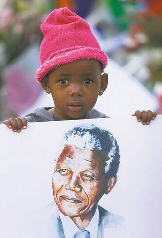 Kagali, 2, with a poster of Nelson Mandela outside the hospital where he is being treated.