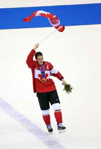 Jonathan Toews scored the winning goal (left) and celebrated with the flag after the game.