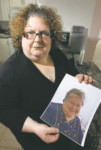 Dana Brenan holds a photo of her mother, Heather Brenan, who died after being sent home from hospital alone and without her house keys on Jan. 27.