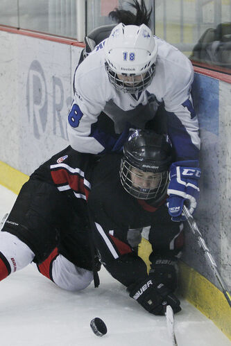 The Westwood Warriors' Alicia Prociuck gets checked by the Lord Selkirk Royals' Ari Kowalchuck in Game 2 of the WWHSHL Division B final Tuesday.