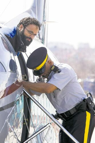 Chiheb Esseghaier is led off a plane by an RCMP officer near Toronto on Tuesday.