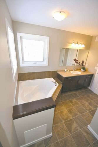 A maple vanity, two windows over a corner jetted tub and shower with vinyl surround and two seats come standard in the elegant ensuite.