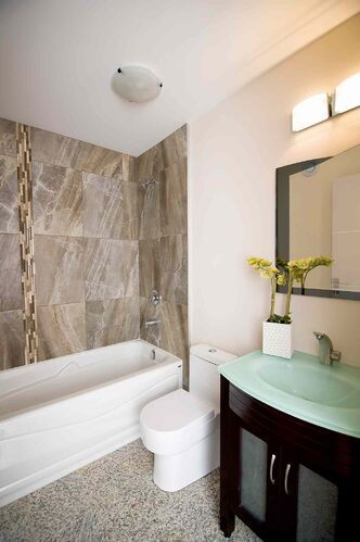 The main bath features travertine tiles and an espresso maple vanity with glass countertop.