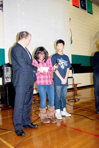 Salisbury Morse Place School Grade 7 student Sarah Mohammed smiles as she and classmate Vincent Tran hand over a $2000 donation to Canadian Red Cross provincial director Shawn Feely. The money will go toward relief efforts in the Philippines.
