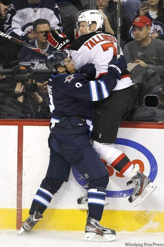 The Winnipeg Jets' Evander Kane (9) takes out New Jersey Devils' Henrik Tallinder (7) during second period NHL action in Winnipeg on Saturday.