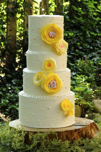 In this undated publicity photo provided by Lauren Karnitz Studio, a Yellow Blooming Peonies Cake is shown in Knoxville, Tenn. Brides are choosing plastic recycled flowers that are affordable and eco-friendly for cakes, bouquets, corsages and boutonnieres. (AP Photo/Lauren Karnitz Studio, Bert Henry)