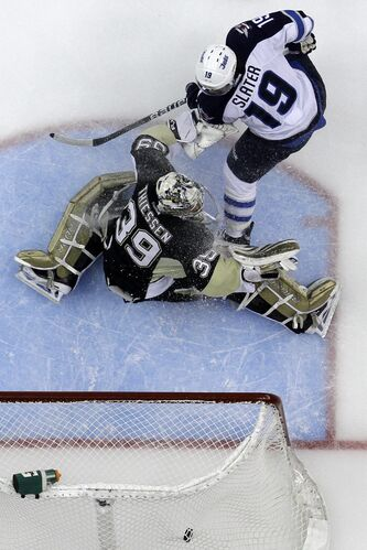 Winnipeg Jets' Jim Slater puts the puck behind Pittsburgh Penguins goalie Brad Thiessen for a goal during the first period of their NHL game in Pittsburgh Tuesday. The Penguins won 8-4.