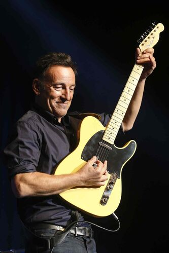 Musician Bruce Springsteen plays a guitar intended for auction at the Stand Up for Heroes event at Madison Square Garden, Thursday, Nov. 7, 2013, in New York. (John Minchillo/Invision/AP)