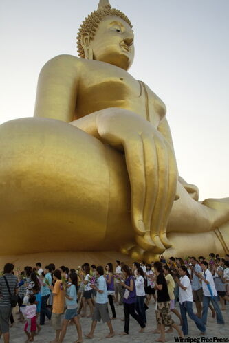 The faithful gather to pray at the base of a giant Buddha statue at Wat Muang in Angthong, Thailand, for Macha Bucha Day ceremonies. Macha Bucha Day is a national holiday in Thailand.