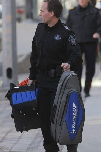 A police officer holds a bag found at Winnipeg Square.