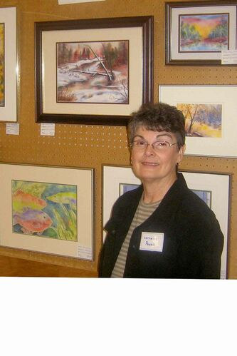 Prairie Palette Art Group member Lorraine Powell stands next to her paintings at the group's annual show, held in Oak Bluff in May each year. The group is currently seeking new members.