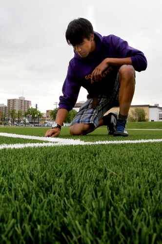 Grade 10 Gordon Bell High School student Jonathan Prince feels the new artificial turf covering the school's field.