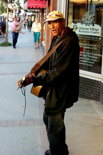 Eric Pyle, with guitar in hand, has been serenading people in Osborne Village for nearly a decade.