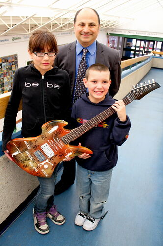 King Edward School students Sheri Shorting and Leo Blyth, with principal Aaron Benarroch. The school is auctioning off a custom-made guitar autographed by the Winnipeg Jets to help raise the money needed for a park-like overhaul of its schoolyard. Last May, vandals destroyed the school's play structure, leaving students with next to no alternatives.