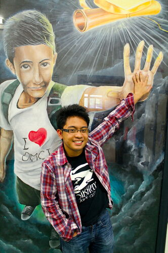 Christian Miranda joins hands with one of his murals at DMCI. Seven of his paintings, along with hundreds of artworks by fellow classmates, will be shown at DMCI for their Celebration of the Arts 2013 show June 6 and 7.