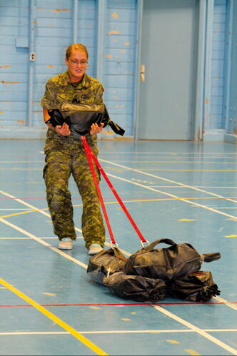 Pte. Amanda Horton drags 100 kilos of sand while carrying another 20.