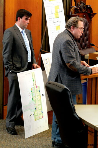 Nick Pavel (left) listens as his architect Larry Silver speaks at a public hearing in support of his development proposal on April 9.