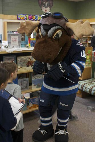 Winnipeg Jets mascot Mick E. Moose signs a copy of The Home Team for a young fan at Princess Margaret School. Centre Mark Scheifele and defenceman Zach Bogosian also attended the I Love to Read Month event through the team's Reading Takes Flight program.