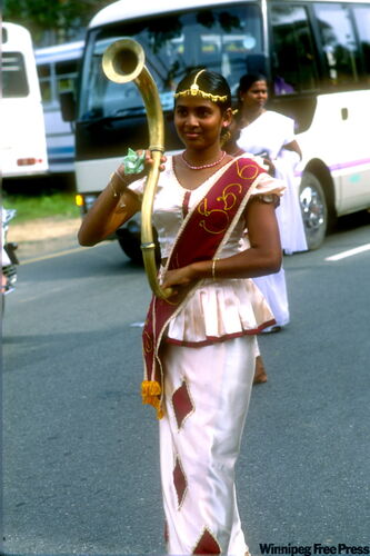 Sri Lankans love processions. A young woman at Unawatuna in a procession to a temple to mark a full moon.