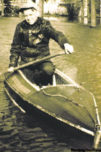 Bill Mason paddles down Oakwood Avenue in Winnipeg during the flood of 1950 in the first canoe he made.