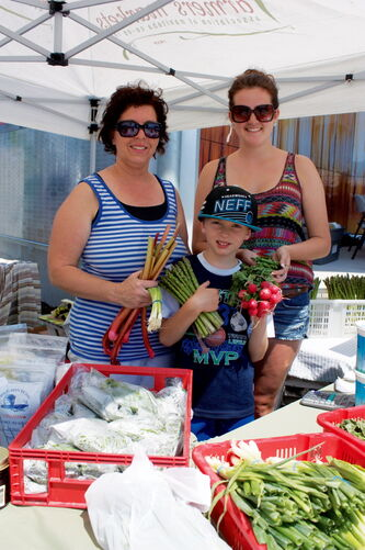 Thelma Neumann, Ty Neumann, and Jessica Bonneteau of Neumann's Market display their wares at the Transcona BIZ Market Garden on July 4.