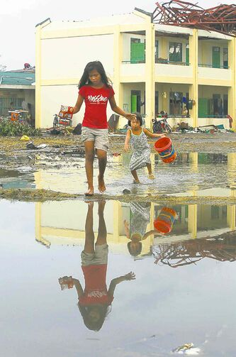 Young girls cross a flooded schoolyard now being used as a makeshift shelter.