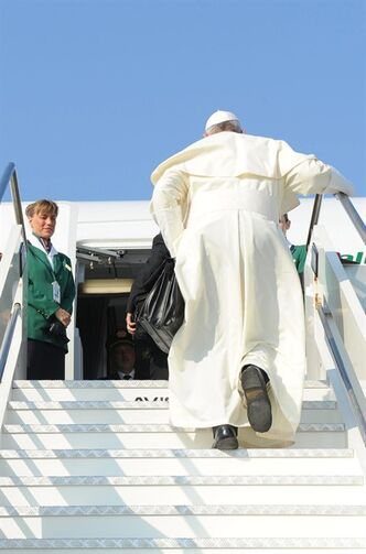 In this photo provided by the Vatican newspaper L'Osservatore Romano, Pope Francis holds a bag as he boards a plane at Rome's Leonardo Da Vinci international airport, Monday, July 22, 2013. It's wheels up on Pope Francis' first trip abroad as pontiff. A special Alitalia flight carrying Francis, his entourage and journalists who will cover him on his week-long visit to Brazil took off 10 minutes behind schedule Monday from Rome's Leonardo da Vinci airport. Keeping to his example that the Catholic church must be humble, Francis carried his own black hand luggage. He even kept holding it with his left hand while he used his left to shake hands with some of the VIPs who turned out to wish him well and while he climbed the stairs to the jet's entrance. Among the dignitaries was Italian Premier Enrico Letta. (AP Photo/L'Osservatore Romano, ho)
