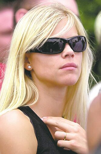 FILE - This is a May 16, 2004, file photo showing Elin Nordegren, Tiger Woods finance, looking on as Woods putts on the third green during the Byron Nelson Championship, in Irving, Texas. The Woods sex scandal has indeed struck a particularly raw nerve in Sweden, where Nordegren's transition from being a nanny for golfer Jesper Parnevik to the wife of one of the world's most famous athletes was long seen as a fairy-tale romance. (AP Photo/Tony Gutierrez, File)