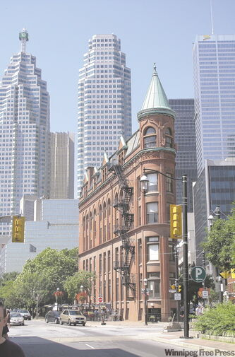 The Goodham Building, otherwise known as Toronto's flatiron building, shown against a backdrop of modern buildings on Front Street.