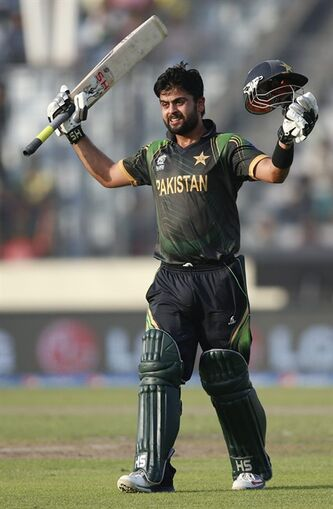 Pakistan batsman Ahmed Shehzad raises his bat and helmet to celebrate scoring a century during their ICC Twenty20 Cricket World Cup match against Bangladesh, in Dhaka, Bangladesh, Sunday, March 30, 2014. (AP Photo/Aijaz Rahi)